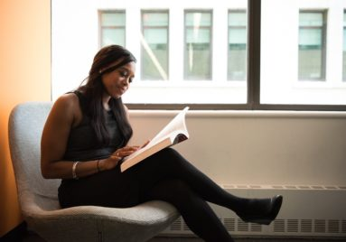 black woman doing research relaxed in library