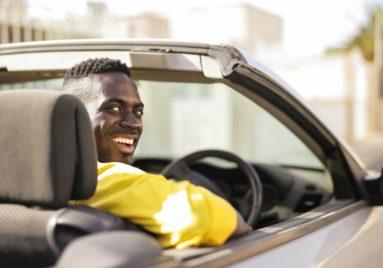 black man driving car turning around to smile