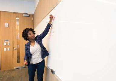 black woman teacher writing on whiteboard