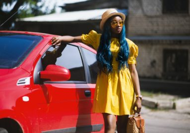 black woman dressed for summer standing next to her car