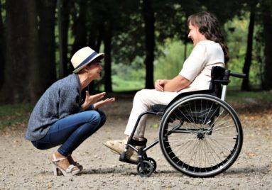 person smiling excited to see their friend who is in a wheelchair