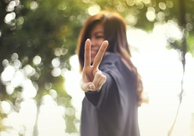 asian woman making a peace sign