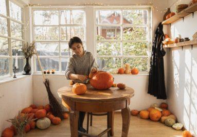 woman carving pumpkin for halloween