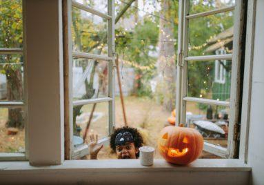 child saying boo next to halloween jackolantern perched on window